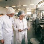 dos profesionales calidad uniformes esteriles blancos que verifican calidad barras sal mientras estan pie fabrica alimentos 232070 405
