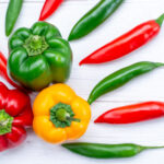 top close view of colorful bell peppers with spicy peppers on light desk vegetable spice hot food meal ingredient product