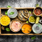 various canned products in tin cans on wooden tray on rustic background 1