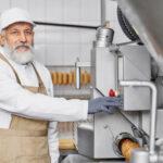 worker of meat factory posing near modern equipment 1