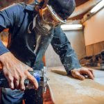 carpenter using circular saw for cutting wooden boards construction details of male worker or handy man with power tools