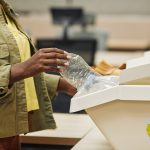 close up of unrecognizable african american woman putting plastic bottle into waste sorting bin in office copy space
