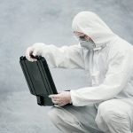 laboratory technician in mask and chemical protective suit opens toolbox on dry land