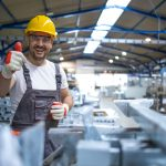 portrait of factory worker in protective equipment holding thumbs up in production hall