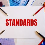 the word standards is written on white wall near colored graphs pens and pencils business concept