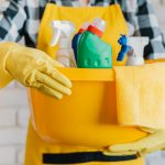 adult holding basket with cleaning products