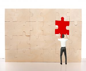 businessman complete puzzle inserting missing red piece