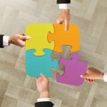 businessmen working together to build colored puzzle