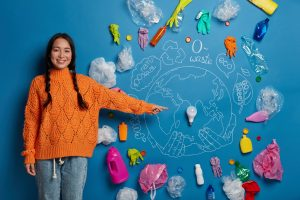 friendly looking korean woman indicates at light bulb asks to collect trash and reduce using plastic items involved in cleaning campaign cares for environment