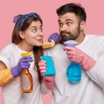 funny european wife and husband hold mop and bottle of spray wear rubber protective gloves