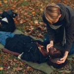 guy help woman afro girl is lying unconscious providing first aid in the park