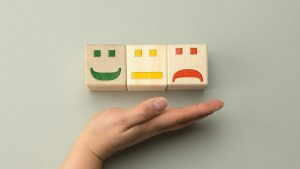 wooden blocks with different emotions from smile to sadness and woman s hand concept for assessing the quality of product or service emotional state user reviews