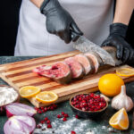 front view cook in apron cutting raw fish on cutting board vegetables on wood board on table